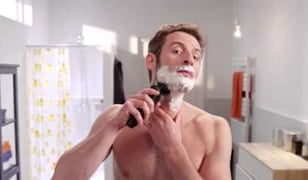 A man shaving using a Philips electric shaver